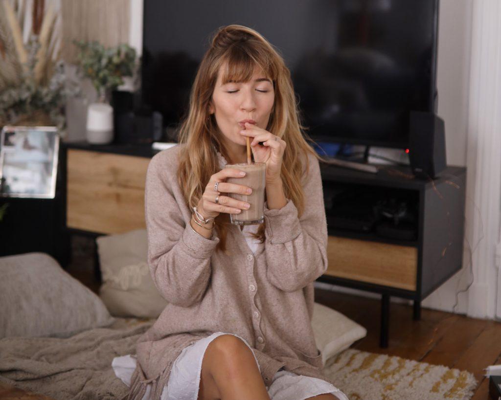 jeune femme dégustant un smoothie banane, fruits rouges, amande, dattes, healthy et gourmand à la maison