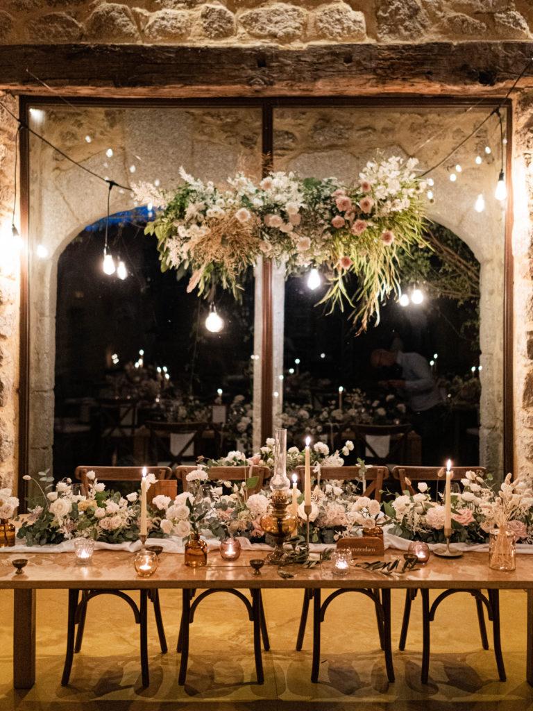table d'honneur de mariage dans le thème romantique avec un centre de table de fleurs.